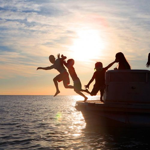Kids jumping off a boat at sunset